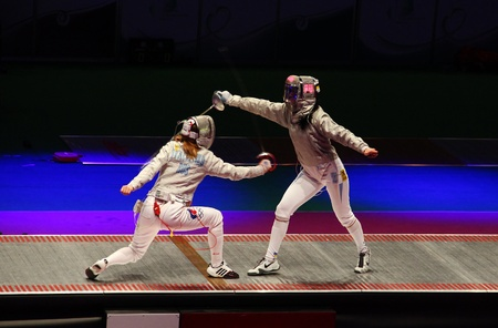 KYIV, UKRAINE - APRIL 13: Ekaterina Dyachenko (Russia) fights against Olena Khomrova (Ukraine) during women's sabre team final match of the World  Fencing Championships on April 13, 2012 in Kyiv, Ukraine Stock Photo - 13257411