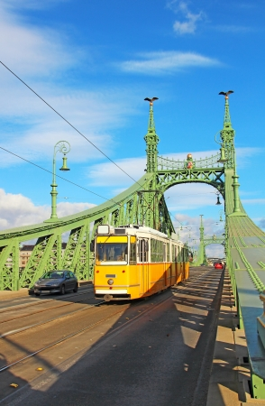 Orange tram on the Liberty bridge over Danube river in Budapest, Hungary Stock Photo