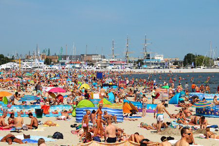 GDYNIA, POLAND - AUGUST 2, 2015: Crowded public beach in Gdynia on Baltic sea Редакционное