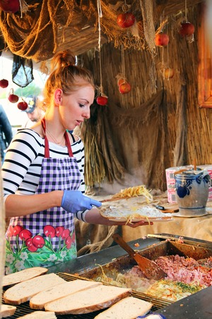 GDANSK, POLAND - JULY 29, 2015: Young woman makes traditional sandwich with lard spread, onions, sausage and cucumbers on the summer fair in downtown Gdansk