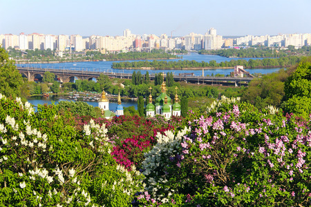 Spring view of Kyiv with Vydubychi monastery, Darnytsky bridge over Dnipro river, and lilac blossom in botanical garden Stock Photo