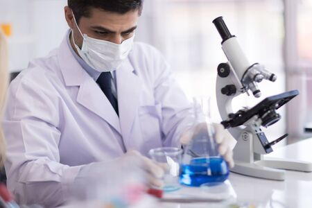 A male scientist wearing a mask and looking through the microscope in the laboratory