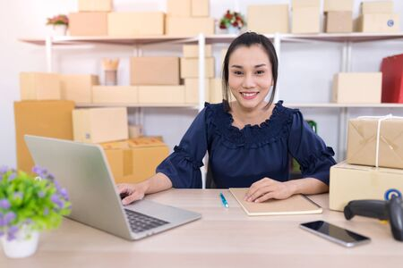 Asian women who are SME online shopping operators siting and looking at the camera. Online shopping SME entrepreneur or freelance working concept.