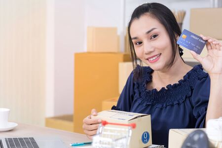 Asian women who are online shopping operators SME smile confidently and holding credit card on hand, SME online shopping entrepreneurs or freelance concept
