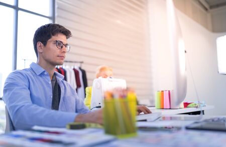 Young men wear glasses as clothing designers. Currently working in a clothing store