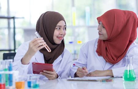Two female muslim scientists wear white coat with reagent during experiment in chemical lab. Archivio Fotografico