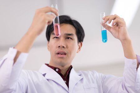 Asian scientists wearing white coats Holding a research glass tube And with a startled face Stock fotó