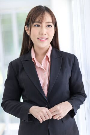 Beautiful Asian businesswomen wearing a black suit standing in the office, smiling confidently. Asian business women, Executive new generation, Business owners, and office staff. Concept 版權商用圖片