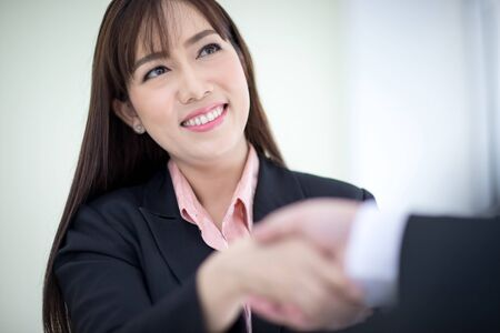 Beautiful Asian business woman wears a black suit and hand in hand with a partner and smile confidently.  Asian business women, Executive new generation, Business owners, and office staff. Concept 版權商用圖片