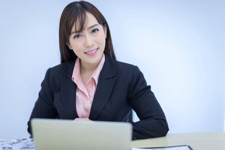 Beautiful Asian businessman wearing a black suit sitting in the office, smiling confidently and looking at the camera. Asian business women, business owners, and office staff. Concept 版權商用圖片