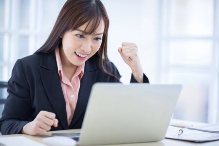 Beautiful Asian business woman wore a black suit sitting in the office, smiling happily when the job project was successful. Asian business women, business owners and office workers. Stock Photo