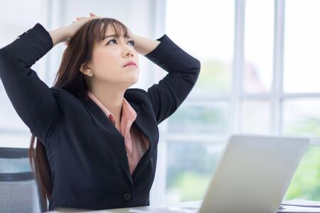 Beautiful Asian women disappointed with the job project. There is a laptop on the table in office. Asian business women, employee, and office staff. Concept