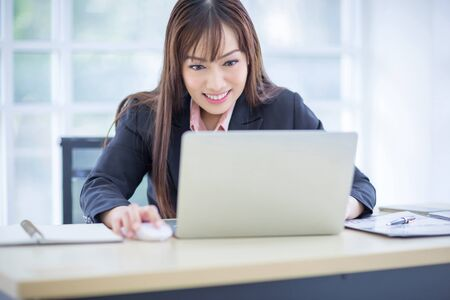 Beautiful Asian business woman wore a black suit sitting in the office, smiling happily when the job project was successful. Asian business women, business owners and office workers.