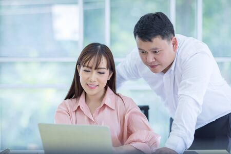 Two Asian business men and women looking at the laptop and talking about work projects at office. Asian business people, employee, and office staff. Concept 版權商用圖片