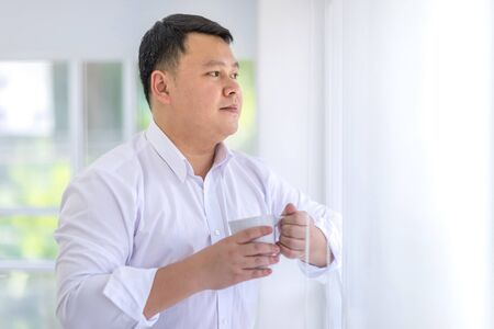 Asian Men wearing a white shirt is holding a white coffee cup and look out the window. Stock Photo