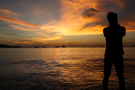 silently: silhouette of photographer at sunset on the Pattaya beach, Thailand