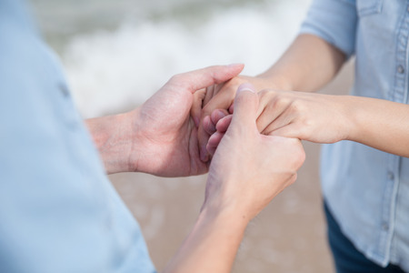 Couple holding hand by the sea photo
