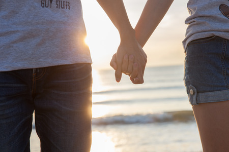 Holding hand while sunset by the sea