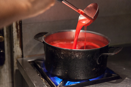 estufa: chef preparando salsa rosa Foto de archivo