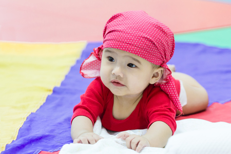 prone: asian baby prone on colorful fabric, child age 4 months learning to lie down