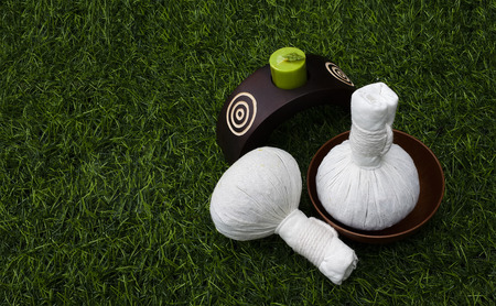 scented candle: set of herbal ball and scented candle on greensward with spa concept and copy space