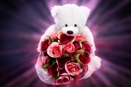 spacial: Selective focus at bouquet of beautiful artificial red roses in the arms of blurry  bear doll  on black background and pink ray light effect, concept love for valentine day or spacial  anniversary