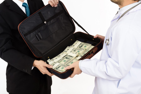 Man in black suit is given a bag containing a lot of money to doctor on white background, Business concept Corruption in health care industry or Donates to health