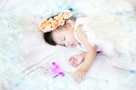 scepter: A mestizo lovely girl dressed as a fairy has a crown pastel flowers on her head sleeping and magic scepter in her hand on the couch white, and white feather place surrounded and copy space Stock Photo