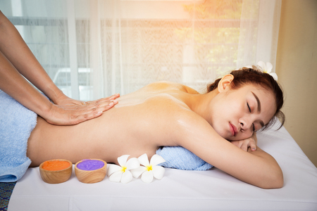Beautiful asian young woman lying on a spa bed, and masseuses hands were massaging on her back, spa concept