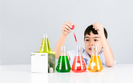 Asian little boy having fun in the liquid droplets red into the test beaker on white table and background,  Easy Science experiment for children, Education concept