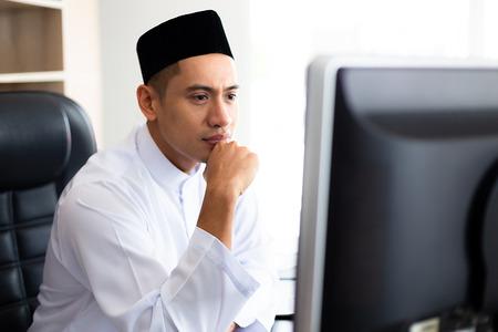 Jonge knappe moslimzakenman die met de computer op kantoor werkt, hij kijkt naar een grote monitor met de bedoeling, kopieer ruimte