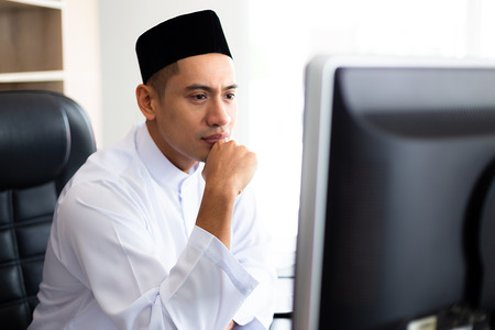 Young handsome muslim businessman working with computer at the office, He looking a large monitor with the intention, copy space