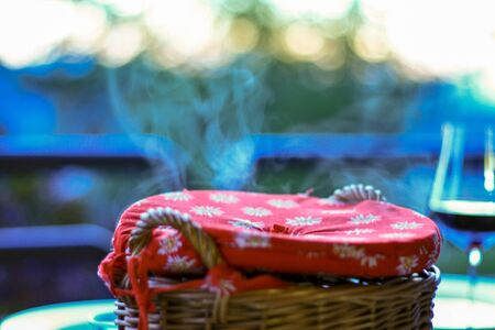 Wooden basket with hot food with steam rising and sunset in the background. Dinner served at home on a terrace