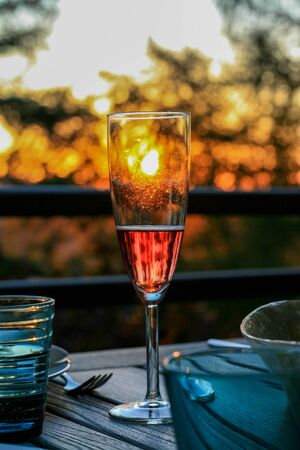 Glass of champagne or wine on table on terrace during evening. Sunset and trees in the background. Home comfort, relaxation, calm, tranquility. Enjoying stay at home.