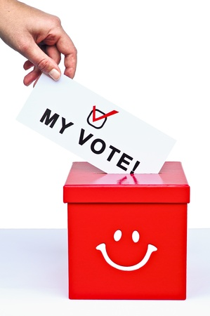 Hand putting a voting ballot in a slot of box photo