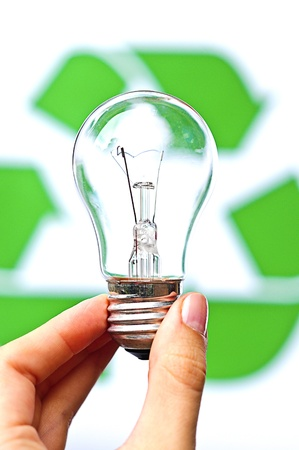 Bulb in a hand against recycling sign background
