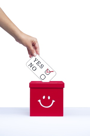 local council election: Hand putting a voting ballot in a slot of box