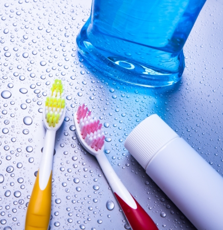 Two toothbrushea, toothpaste and mouthwash with waterdrops Stock Photo