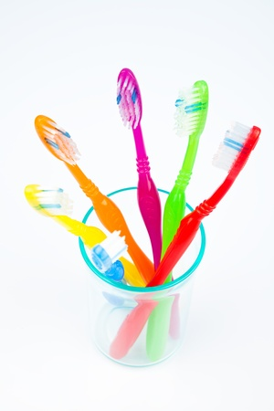 Five colorful toothbrushes in a water glass photo