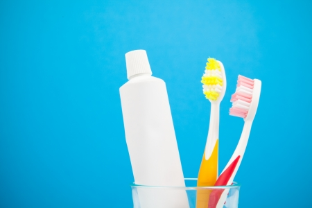 Two colorful toothbrushes and toothpaste in water glass Stock Photo