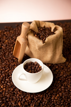 cup of coffee and burlap sack on roasted coffee beans Stock Photo