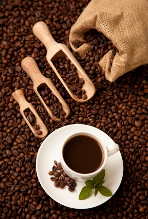Wooden shovels full of coffee with burlap sack and a cup of coffee Stock Photo