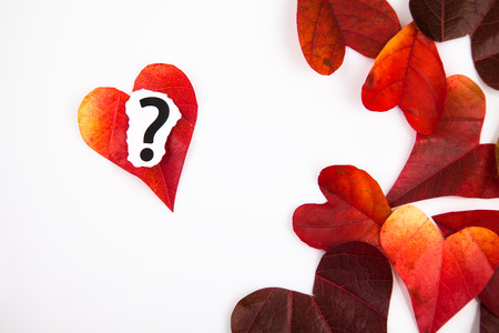 attac: Heart shaped leaves  and a question mark background Stock Photo