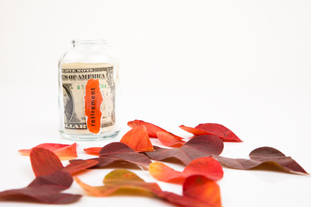 Jar for savings with autumn heart shaped leaves photo