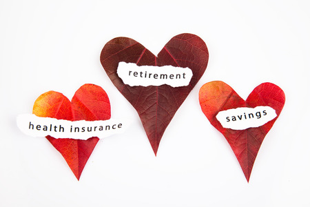 Heart shaped leaves with signs health insurance, retirement, savings background Stock Photo
