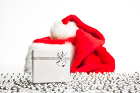 A gift box standing next to Santa Claus red hat