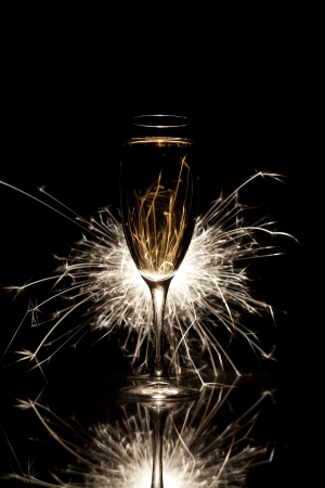 Glass of champagne and burning sparkler Stock Photo