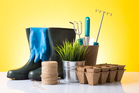 Garden equipment  boots, rake, shovel, pot, plant  over yellow background photo