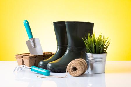 Garden equipment  boots, rake, shovel, pot, plant  over yellow background photo