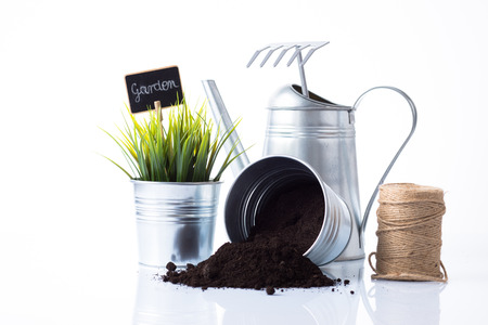 Subtle metal gardening items, plant and cord composition isolated on white
